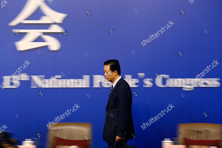 China's Finance Minister Xiao Jie arrives for a press conference on the sidelines of the National People's Congress at the media center in Beijing, . Xiao tried Wednesday to defuse concern over the country's rising debt, saying government borrowing is below danger levels and regulators can prevent financial system risks