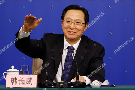 China's Agriculture Minister Han Changfu gestures as he speaks during a press conference on the sideline of the National People's Congress at the media center in Beijing