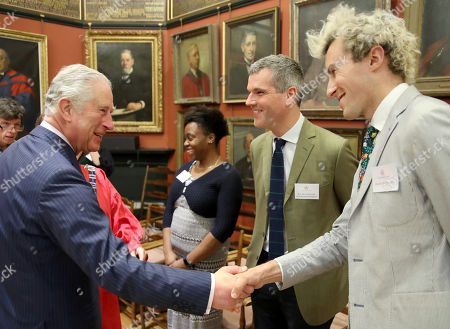 Stock Image of Prince Charles (L) talks to Architectural Designer Ben Pentreath (2ndR) and Charlie McCormormick (R) visits the Art Worker's Guild