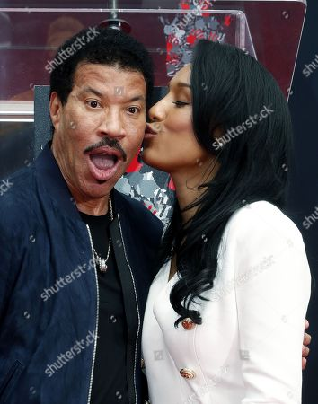 US musician Lionel Richie (L) is kissed by his girlfriend Lisa Parigi (R) during a ceremony honoring him with his hands and footprints in cement outside the TCL Chinese Theatre in Hollywood, California, USA, 07 March 2018.