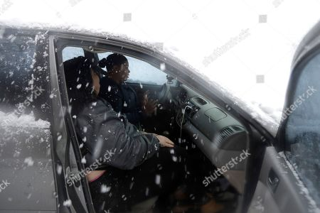 Elizabeth Zaldana, center, sits behind the wheel of her vehicle with friend Noelia Lozada after the two were plowed in by a plow truck along the ramp connecting Interstate-80 and Interstate-287, in Parsippany, N.J. Zaldana, of Newark, was on her way to pick up her boyfriend from his work when she became stuck on the northbound of Interstate-287