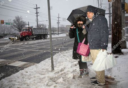 Christopher Martinez, right, waits with Jessica Suarez for her bus as a snow plow passes by in North Bergen, N.J
