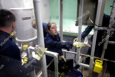 U.S. Navy Ensign Megan Stevenson, of Raymond, Maine, center, works with other U.S. Navy officers to patch high-pressure leaking pipes inside a replica of a submarine engine room during a damage control training exercise at the Naval Submarine School, in Groton, Conn. The Navy began bringing female officers on board submarines in 2010, followed by enlisted female sailors five years later. Their retention rates are on par with those of men, according to records obtained by The Associated Press
