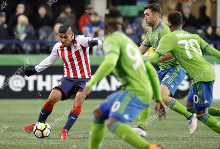 Guadalajara defender Carlos Salcido, left, kicks the ball during the first half of the team's CONCACAF Champions League soccer match against the Seattle Sounders, in Seattle