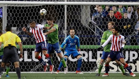 As Seattle Sounders goalkeeper Stefan Frei, center, watches, Guadalajara defender Carlos Salcido (3) and Sounders defender Will Bruin (17) vie for a head ball near the goal during the second half of a CONCACAF Champions League soccer match, in Seattle. The Sounders won 1-0
