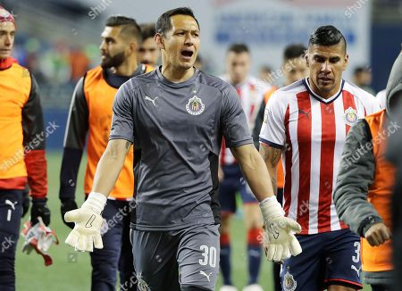 Guadalajara goalkeeper Rodolfo Cota, center, reacts as he walks off the pitch with defender Carlos Salcido, right, following the team's CONCACAF Champions League soccer match against the Seattle Sounders, in Seattle. The Sounders won 1-0