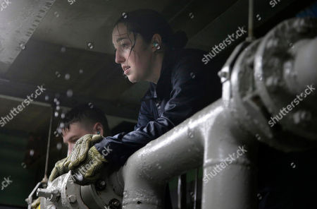 U.S. Navy Ensign Megan Stevenson, of Raymond, Maine takes a rest after working with other U.S. Navy officers to patch high-pressure leaking pipes inside a replica of a submarine engine room during a damage control training exercise at the Naval Submarine School, in Groton, Conn. The Navy began bringing female officers on board submarines in 2010, followed by enlisted female sailors five years later. Their retention rates are on par with those of men, according to records obtained by The Associated Press