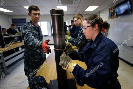 U.S. Navy Petty Officer First Class Clinton Benson, of Stanton, Mich., left, speaks to U.S. Navy Ensign Megan Stevenson, of Raymond, Maine, right, as Stevenson trains to patch high-pressure pipe leaks during a class at the Naval Submarine School, in Groton, Conn. The Navy began bringing female officers on board submarines in 2010, followed by enlisted female sailors five years later. Their retention rates are on par with those of men, according to records obtained by The Associated Press
