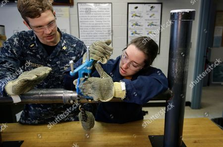 U.S. Navy Ensigns Thomas Patterson, of Anaheim, Calif., left, and Megan Stevenson, of Raymond, Maine, train to patch high-pressure pipe leaks during a class at the Naval Submarine School, in Groton, Conn. The Navy began bringing female officers on board submarines in 2010, followed by enlisted female sailors five years later. Their retention rates are on par with those of men, according to records obtained by The Associated Press