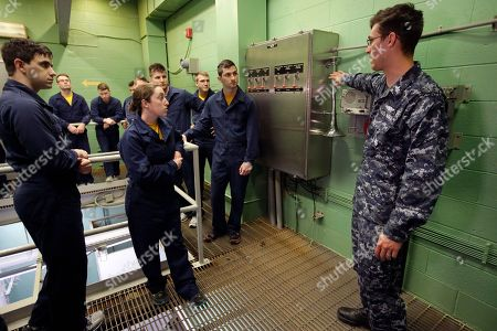 U.S. Navy Petty Officer First Class Clinton Benson, of Stanton, Mich., right, speaks to a class, including U.S. Navy Ensign Megan Stevenson, of Raymond, Maine, center left, at the Naval Submarine School, in Groton, Conn. The Navy began bringing female officers on board submarines in 2010, followed by enlisted female sailors five years later. Their retention rates are on par with those of men, according to records obtained by The Associated Press