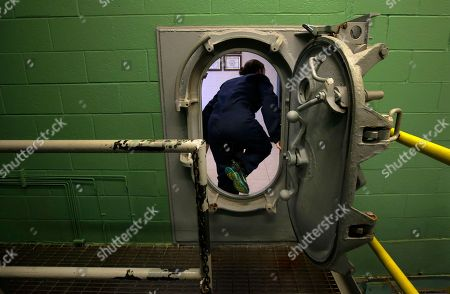 U.S. Navy Ensign Megan Stevenson, of Raymond, Maine, steps through an entrance to a replica of a submarine engine room at the Naval Submarine School, in Groton, Conn., where Stevenson and other U.S. Navy officers participated in a damage control training exercise. The Navy began bringing female officers on board submarines in 2010, followed by enlisted female sailors five years later. Their retention rates are on par with those of men, according to records obtained by The Associated Press