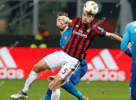 Arsenal's Calum Chambers, left, and AC Milan's Giacomo Bonaventura vie for the ball during the Europa League, round of 16 first-leg soccer match between AC Milan and Arsenal, at the Milan San Siro stadium, Italy