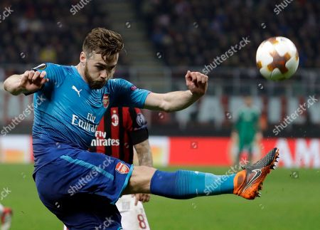 Arsenal's Calum Chambers, front, duels for the ball with AC Milan's Suso during the Europa League round of 16 first-leg soccer match between AC Milan and Arsenal, at the Milan San Siro Stadium, Italy