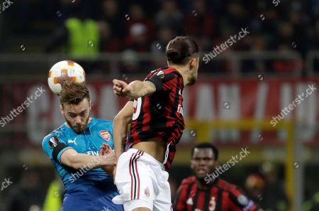 Arsenal's Calum Chambers, left, jumps for the ball with AC Milan's Ricardo Rodriguez during the Europa League round of 16 first-leg soccer match between AC Milan and Arsenal, at the Milan San Siro Stadium, Italy