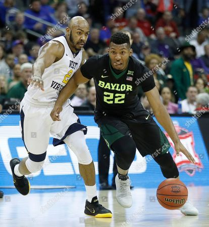 Baylor's King McClure (22) drives under pressure from West Virginia's Jevon Carter (2) during the first half of an NCAA college basketball game in the Big 12 men's tournament, in Kansas City, Mo
