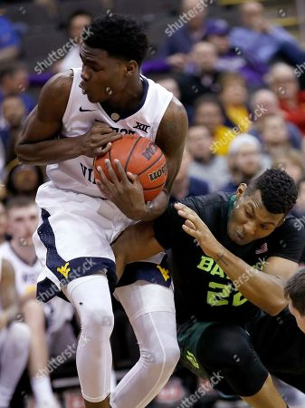 Baylor's King McClure, right, tries to steal the ball from West Virginia's Wesley Harris during the second half of an NCAA college basketball game in the Big 12 men's tournament, in Kansas City, Mo