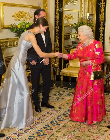 Stock Picture of Queen Elizabeth II meets Princess Salwa Aga Khan in the White Drawing Room at Windsor Castle during a reception before a private dinner to mark the diamond jubilee of the Aga Khan's leadership as Imam of the Shia Ismaili Muslim Community