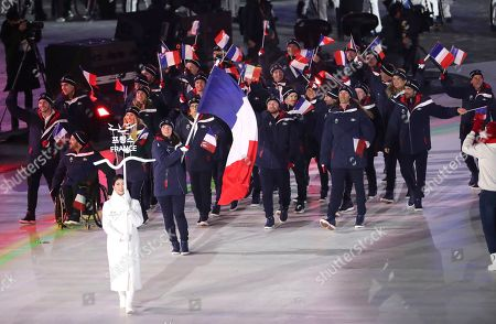 Marie Bochet carries the flag of France as she leads her teammates into the opening ceremony of the 2018 Winter Paralympics in Pyeongchang, South Korea