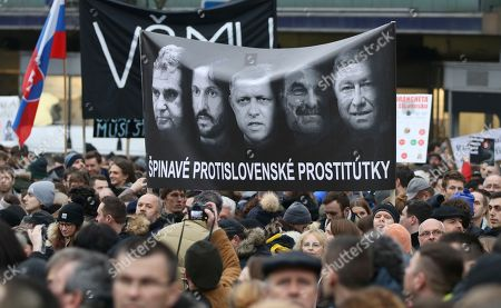 Demonstrators hold a poster reading 'Dirty anti-Slovak prostitutes' with Prime Minister Robert Fico in the middle, his Interior Minister Robert Kalinak (to Fico's right), and national police chief Tibor Gaspar, right, during an anti-government rally in Bratislava, Slovakia, . The country-wide protests demand a thorough investigation into the shooting deaths of Jan Kuciak and Martina Kusnirova, whose bodies were found in their home on Feb. 25, and changes in the government