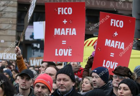 Demonstrators hold posters linking Slovakian Prime Minister Robert Fico to the mafia during an anti-government rally in Bratislava, Slovakia, . The country-wide protests demand a thorough investigation into the shooting deaths of Jan Kuciak and Martina Kusnirova, whose bodies were found in their home on Feb. 25, and changes in the government