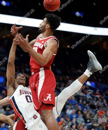 Auburn's Horace Spencer (0) knocks the ball away from Alabama's Braxton Key, top, during the first half in an NCAA college basketball game at the Southeastern Conference tournament, in St. Louis