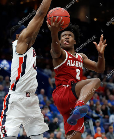 Alabama's Collin Sexton, right, heads to the basket as Auburn's Horace Spencer defends during the second half in an NCAA college basketball quarterfinal game at the Southeastern Conference tournament, in St. Louis. Alabama won 81-63