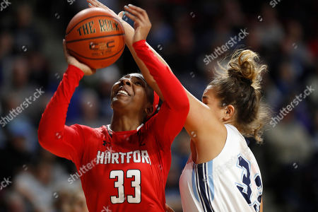 Stock Photo of Janelle Harrison, Kirsten Johnson. Hartford's Janelle Harrison (33) looks to the net as she is guarded by Maine's Kirsten Johnson in the first half in the America East Conference women's basketball championship, in Bangor, Maine