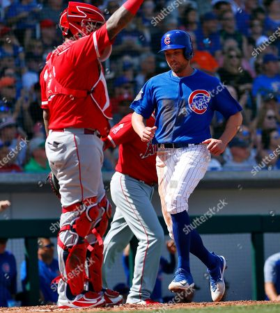 Chicago Cubs' Peter Bourjos scores on an RBI base hit by teammate David Bote as Los Angeles Angels catcher Martin Maldonado waits for the throw during the second inning of a spring training baseball game, in Mesa, Ariz