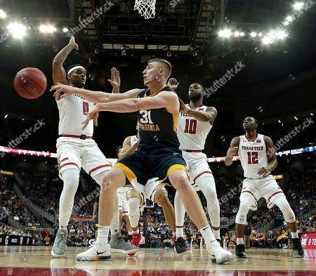 West Virginia's Logan Routt (31) passes the ball past Texas Tech's Tommy Hamilton IV (0) during the first half of an NCAA college basketball game in the semifinals of the Big 12 conference tournament in Kansas City, Mo