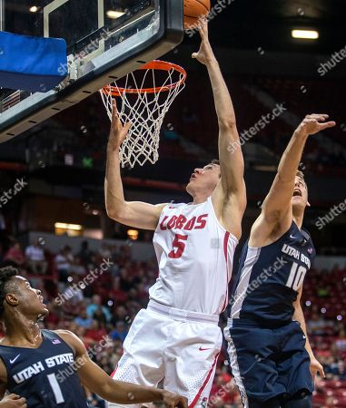 New Mexico forward Joe Furstinger (5) gets inside for a basket over Utah State forward Quinn Taylor (10) during the second period of an NCAA college basketball semifinals game in the Mountain West Conference tournament, in Las Vegas