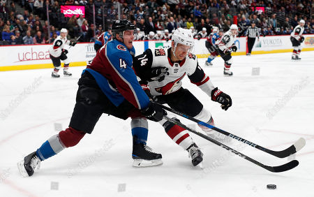 Stock Image of Tyson Barrie, Richard Panik. Arizona Coyotes right wing Richard Panik, right, hits Colorado Avalanche defenseman Tyson Barrie a he tries to bring the puck out his zone in the second period of an NHL hockey game, in Denver