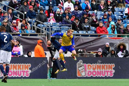 New England Revolution defender Gabriel Somi (91) and Colorado Rapids midfielder Jack McBean (32) collide midair during the MLS game between Colorado Rapids and the New England Revolution held at Gillette Stadium in Foxborough Massachusetts