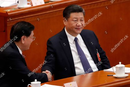 Xi Jinping, Zhang Dejiang. Chinese President Xi Jinping, right, shakes hands with National People's Congress Chairman Zhang Dejiang during a plenary session of the National People's Congress at the Great Hall of the People in Beijing, . China's rubber-stamp lawmakers on Sunday passed a historic constitutional amendment abolishing presidential term limits that will enable Xi to rule indefinitely