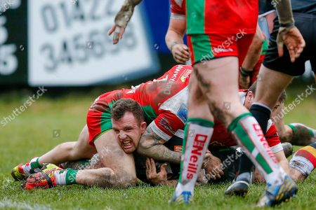 Bradford Bulls interchange George Flanagan (21) is tackled by  a number of Keighley Cougars  players during the Betfred League 1 match between Keighley Cougars and Bradford Bulls at Cougar Park, Keighley. Picture by Simon Davies