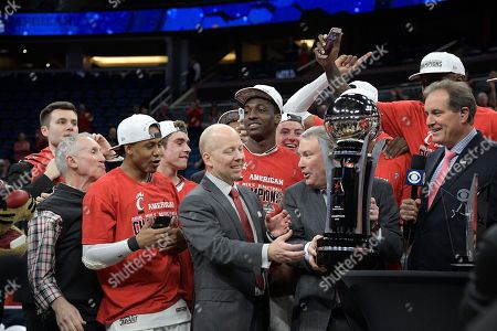 Jim Nantz, Mick Cronin, Michael Aresco. CBS Sports broadcaster Jim Nantz, right, watches as Cincinnati head coach Mick Cronin is presented the championship trophy by AAC commissioner Michael Aresco, second from right, during the trophy presentation after an NCAA college basketball championship game against Houston at the American Athletic Conference tournament, in Orlando, Fla. Cincinnati won 56-55