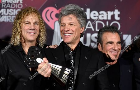 David Bryan, Jon Bon Jovi, Tico Torres. David Bryan, from left, Jon Bon Jovi and Tico Torres, of Bon Jovi, pose in the press room with the Icon award at the iHeartRadio Music Awards at The Forum, in Inglewood, Calif