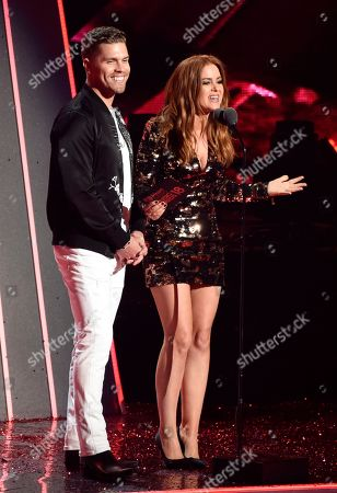 Dustin Lynch, Isla Fisher. Singer Dustin Lynch and actress Isla Fisher address the audience during the 2018 iHeartRadio Music Awards at The Forum, in Inglewood, Calif