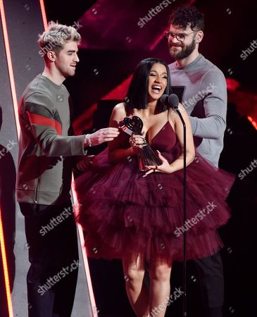 Stock Picture of Alex Pall, Andrew Taggart, Cardi B. Singer Cardi B accepts the Best New Artist award from Andrew Taggart, left, and Alex Pall of The Chainsmokers during the 2018 iHeartRadio Music Awards at The Forum, in Inglewood, Calif
