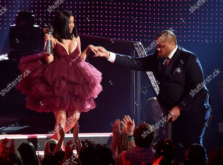 Singer Cardi B is helped exiting the stage after winning Best New Artist during the 2018 iHeartRadio Music Awards at The Forum, in Inglewood, Calif