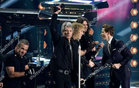Jon Bon Jovi, Shaun White. Jon Bon Jovi, center, accepts the Icon Award with band members during the 2018 iHeartRadio Music Awards at The Forum, in Inglewood, Calif. At right is presenter and U.S. Olympic snowboarder Shaun White