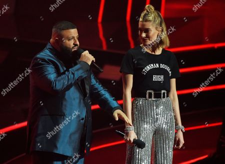 DJ Khaled, Hailey Baldwin. Hosts DJ Khaled, left, and Hailey Baldwin address the audience during the 2018 iHeartRadio Music Awards at The Forum, in Inglewood, Calif