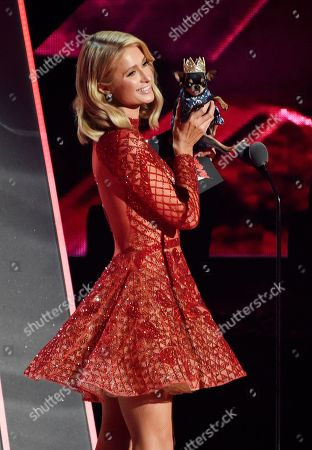 Paris Hilton arrives onstage with her dog Diamond Baby to present the Cutest Musician's Pet award during the 2018 iHeartRadio Music Awards at The Forum, in Inglewood, Calif