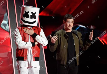 Marshmello, Adam Devine. Dance music producer and DJ Marshmello, left, and actor Adam Devine introduce Maroon 5's performance during the 2018 iHeartRadio Music Awards at The Forum, in Inglewood, Calif