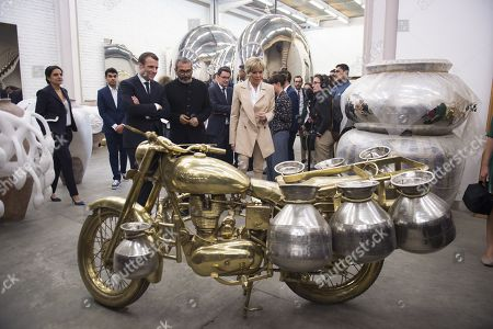 French President Emmanuel Macron (R) and his wife Brigitte Trogneux (C) listen to Indian artist Subodh Gupta (L) during a visit to his showroom
