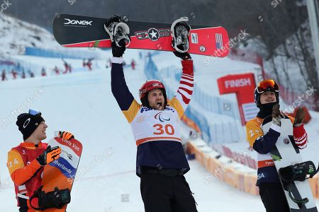 Winners of the Men's Snowboard Cross SB-LL1 event from left silver medalist Chris Vos of Netherlands, gold medalist Mike Schultz of United States and bronze medalist Noah Elliott of United States pose for photos during a ceremony at the 2018 Winter Paralympics in Pyeongchang, South Korea
