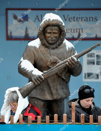 Chris Penne, Jessie Sullivan. From left, Chris Penne of Chena Hills, California and Pennslyvanian Jessie Sullivan read under a statute celebrating the Alaska Territorial Guard prior to the ceremonial start of the Iditarod Trail Sled Dog Race in Anchorage, Alaska