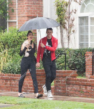 Rachel Levin and Tyler Regan brave the rain with her puppy 'Neyo Bambi'