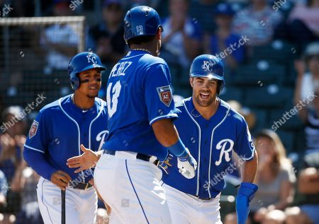 Stock Photo of Kansas City Royals catcher Salvador Perez, center, celebrates with Whit Merrifield, right, and Jon Jay, left, after they scored runs on a double by Michael Saunders against the San Diego Padres during the third inning of a spring training baseball game, in Surprise, Ariz
