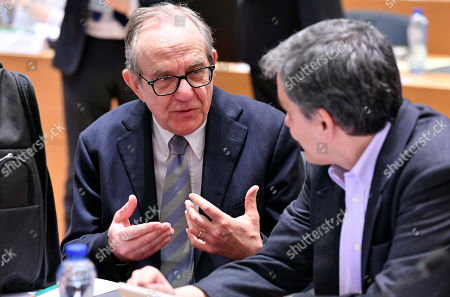 Italian Finance Minister Pier Carlo Padoan, left, speaks with Greek Finance Minister Euclid Tsakalotos during a meeting of EU finance ministers at the Europa building in Brussels