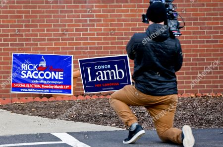 A cameraman takes footage of the signs for the two candidates outside a polling place in the special election being held for the PA 18th Congressional District vacated by Republican Tim Murphy, in McKeesport, Pa. Republican Rick Saccone had just voted at the site. Saccone is running against Democrat Conor Lamb